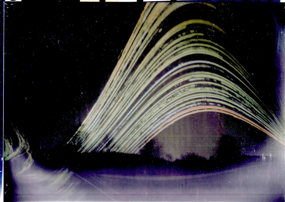 A solargraph image tracks the sun's path over several months.