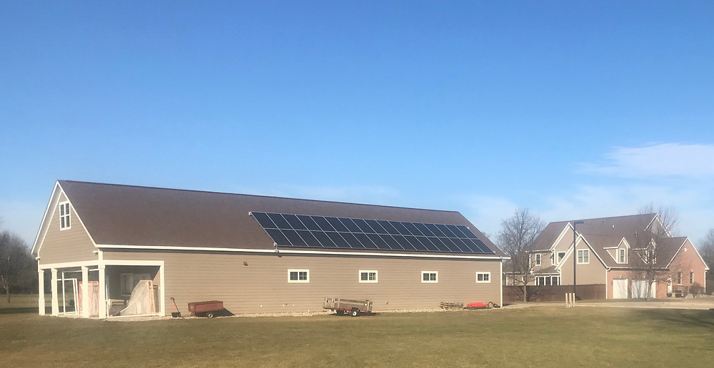 Solar panels atop pole barn send electricity to rectory in background.