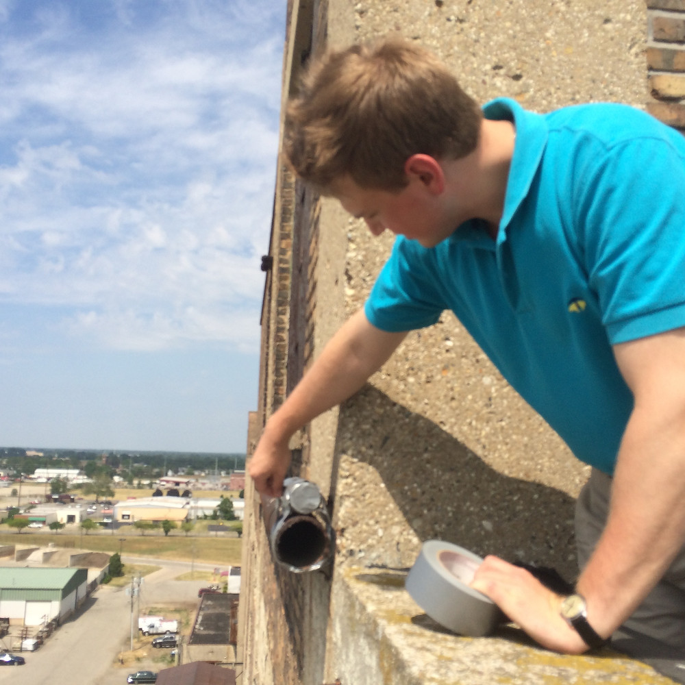 "Will removes tape ""shutter"" from horizontal can atop Building 84."