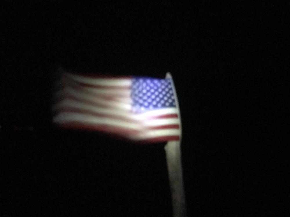 US flag in stiff breeze at night