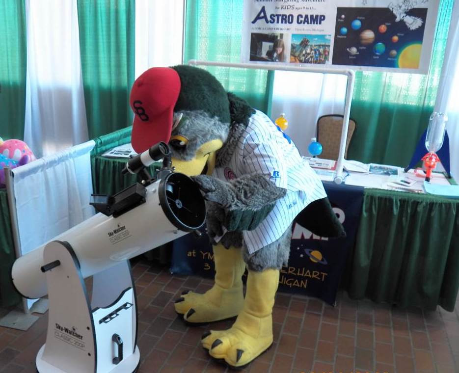 Swoop, a mascot of the South Bend Cubs, checks out a new reflecting telescope from AstroCamp.