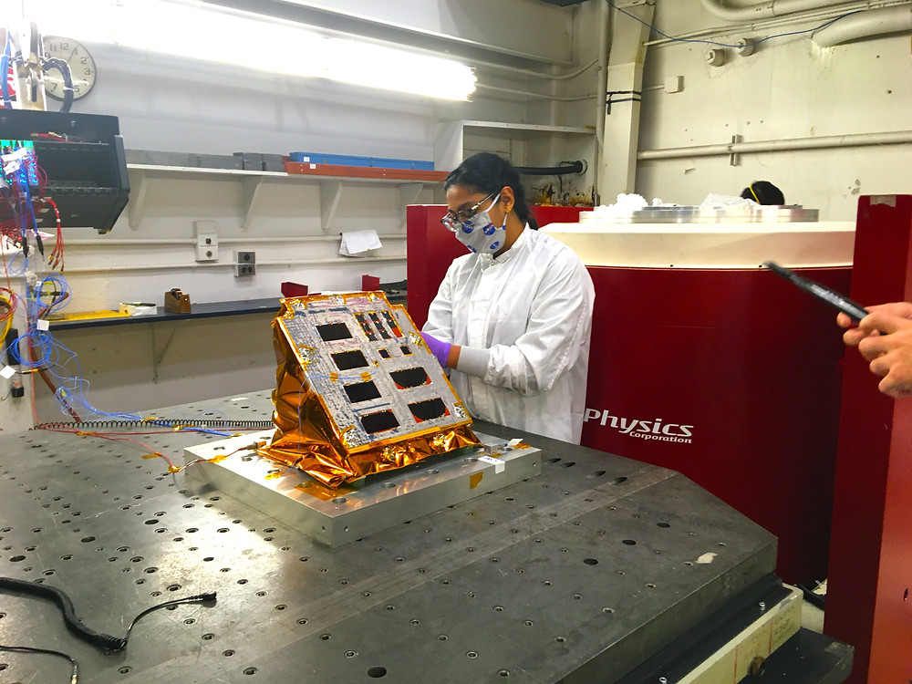 Greeta Thaikattil, lead thermal engineer, checks the installation of the PILS experiment on a vibration table prior to testing at NASA's Glenn Research Center in Cleveland. Credits: NASA
