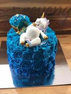 Unicorn eating a cupcake on Rainbow Cake