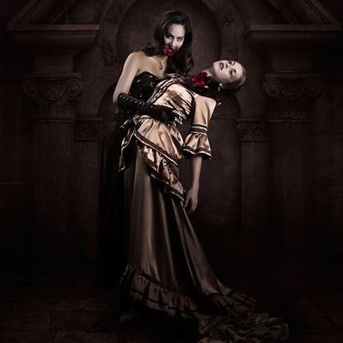Uma vampira olha na direção da câmera enquanto se alimenta de uma mulher em seus braços
