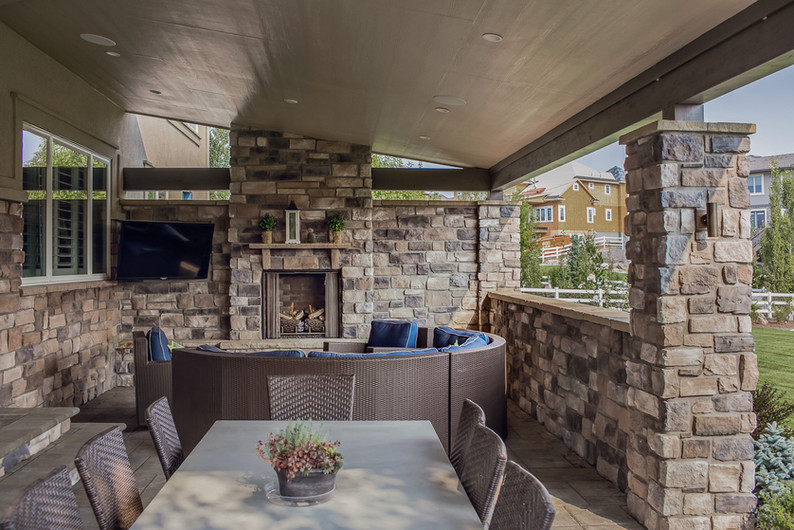 Completely custom roof structure, which encloses the built-in barbecue, fireplace, sitting area, and dining space.