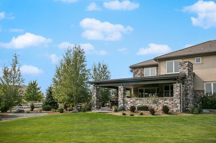 This Broomfield project features a completely custom roof structure, which encloses the built-in barbecue, fireplace, sitting area, and dining space, and an overflow patio with stone fire pit.