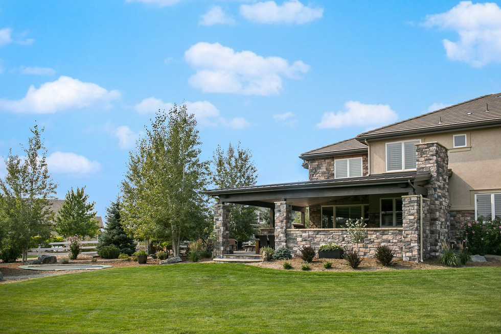 This Broomfield project features a completely custom roof structure, which encloses the built-in barbecue, fireplace, sitting area, and dining space, and anoverflow patio with stone fire pit.