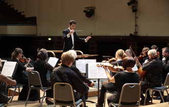 Dominic Grier conducts the Worthing Philharmonic Orchestra. Photo by Mike Austen