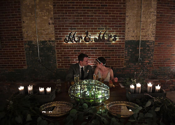 "Donnie &  Eryn at their vintage farm table unde a lighted ""Mr & Mrs"" sign for their reception"