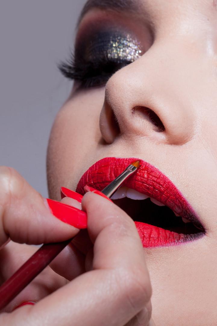 Makeup artist doing lips makeup. Apply l