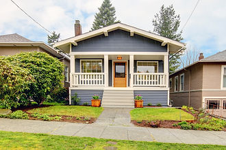 Blue craftsman home with front porch and green lawn