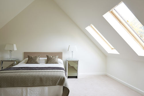 upstairs bedroom, skylights, clean room, brown and white bedding