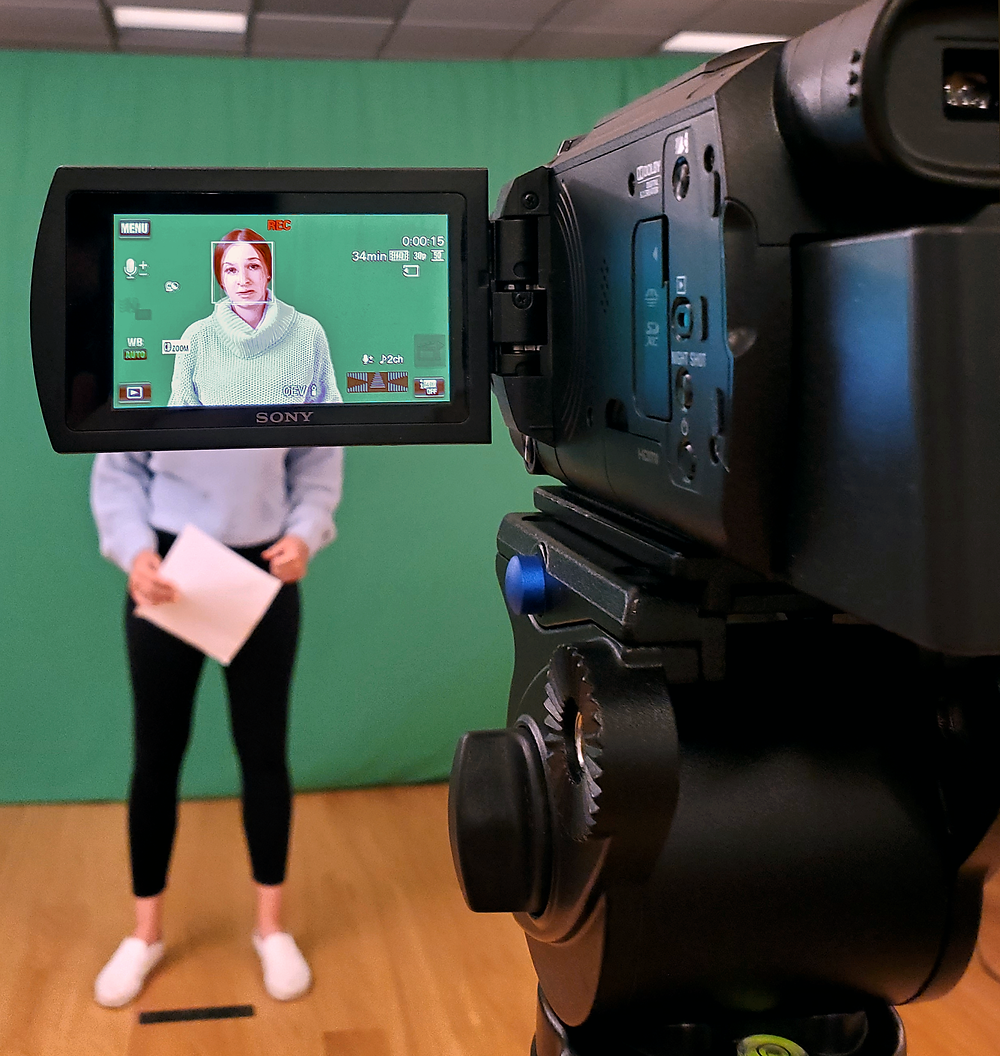 A young woman being recorded by a camera stands in front of a green screen