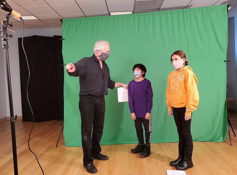 A man in a face mask directs two children in front of a green screen