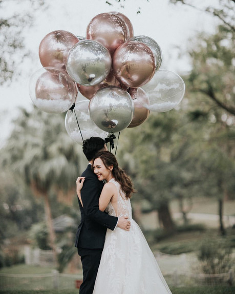 The couple was holding some metallic and transparent balloons during the portrait session after the cake cutting ceremony at Beas River Country Club.