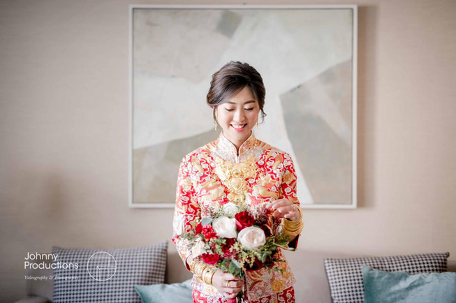 The bride, in a traditional Chinese kua, was taking photo with her bridal bouquet.