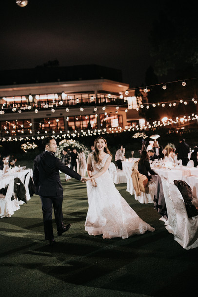 The couple was enjoying the wedding banquet under the overhead lighting designed by Wedding Hashtag.