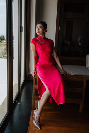 Emi was wearing a qipao in carmine rose with a pair of Jimmy Choo high heels.