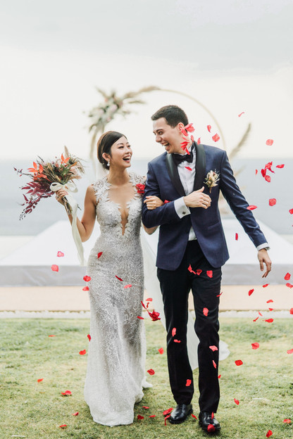 Emi and Chad march out as guests were throwing flower petals in red.