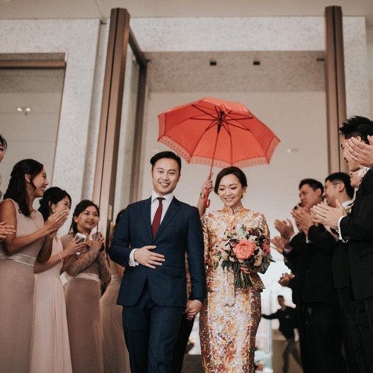 The couple walking out of the hotel as they receive blessing from the wedding party.