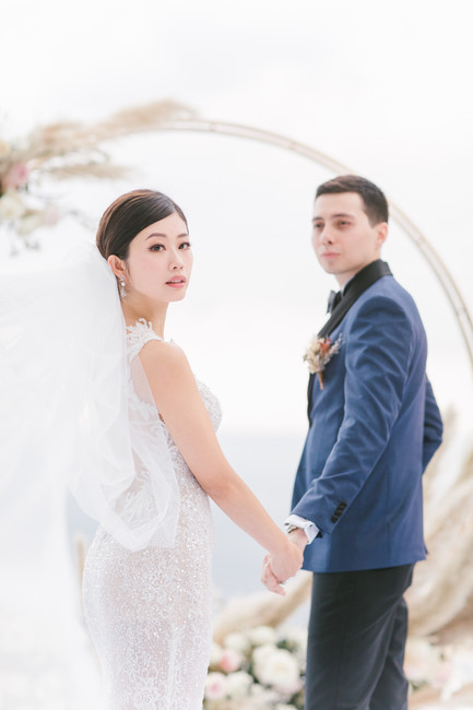 A gorgeous photo of Emi Wong with Chad in front of the pampas grass flower arch.
