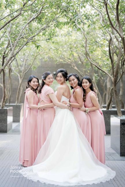 A stunning photo of the bride and bridesmaids under the trees at Grand Hyatt Hong Kong.
