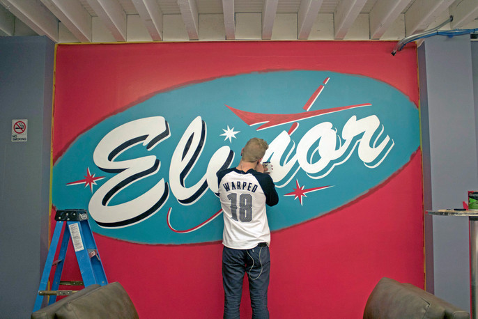 Mid-progress shot of logo mural for Elinor in Downtown Long Beach