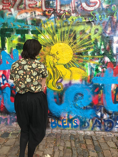 A woman adds her own piece to the famous John Lennon Wall in Prague, Czech Republic