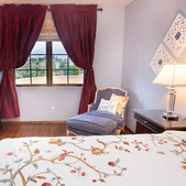 Bedroom 1 has a queen sized bed with hand selected, solid wood collectible dresser and nightstands. Velveteen wine colored drapes let a soft light come through the window.