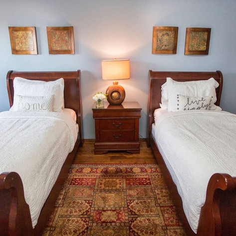 Bedroom 2 holds two single beds with cherry wood frames. A sitting area with leather chairs makes a great place to sit and relax.