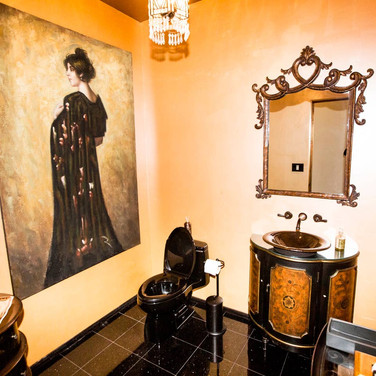A half bath located just off the foyer features stunning artwork, custom mirror and vanity, and bold marble flooring.