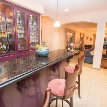 Continuing into the home, the open floor plan is accented by elegant archways. As you step down into the sunken living room, there is a baby grand piano lit by a stunning chandelier for all the music lovers in the family.