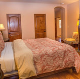In the Master Bedroom you are greeted by warm wood floors, a large walk in closet and a grand king sized bed. The solid wood bed frame, dresser and nightstands match the hand carved hearth and chocolate white marble that surrounds the fireplace.