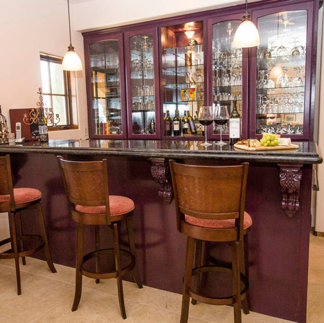 As you travel towards the kitchen you will find the perfect place for happy hour. A wonderful black marble bar with a sink and barstools invites you to sit and enjoy a glass of port or brandy from our custom wine glass collection.