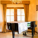 A grand piano lit by a stunning chandelier is waiting to be played by the musician in your family.