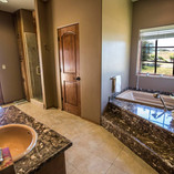 The Master Bath is spacious with natural light and marble which houses his and hers vanity sinks and a beautiful jacuzzi tub set underneath a window. An oversized shower lined with travertine tile has dual shower heads and a built in seat.
