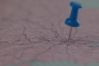 close-up-shot-push-blue-pin-pointing-map