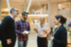 Two men talking to two ladies in an office environment