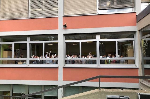 Verabschiedung der 4.Klassen am letzten Schultag - Die Kinder aus den anderen Klassen winken aus den Klassenzimmerfenstern.