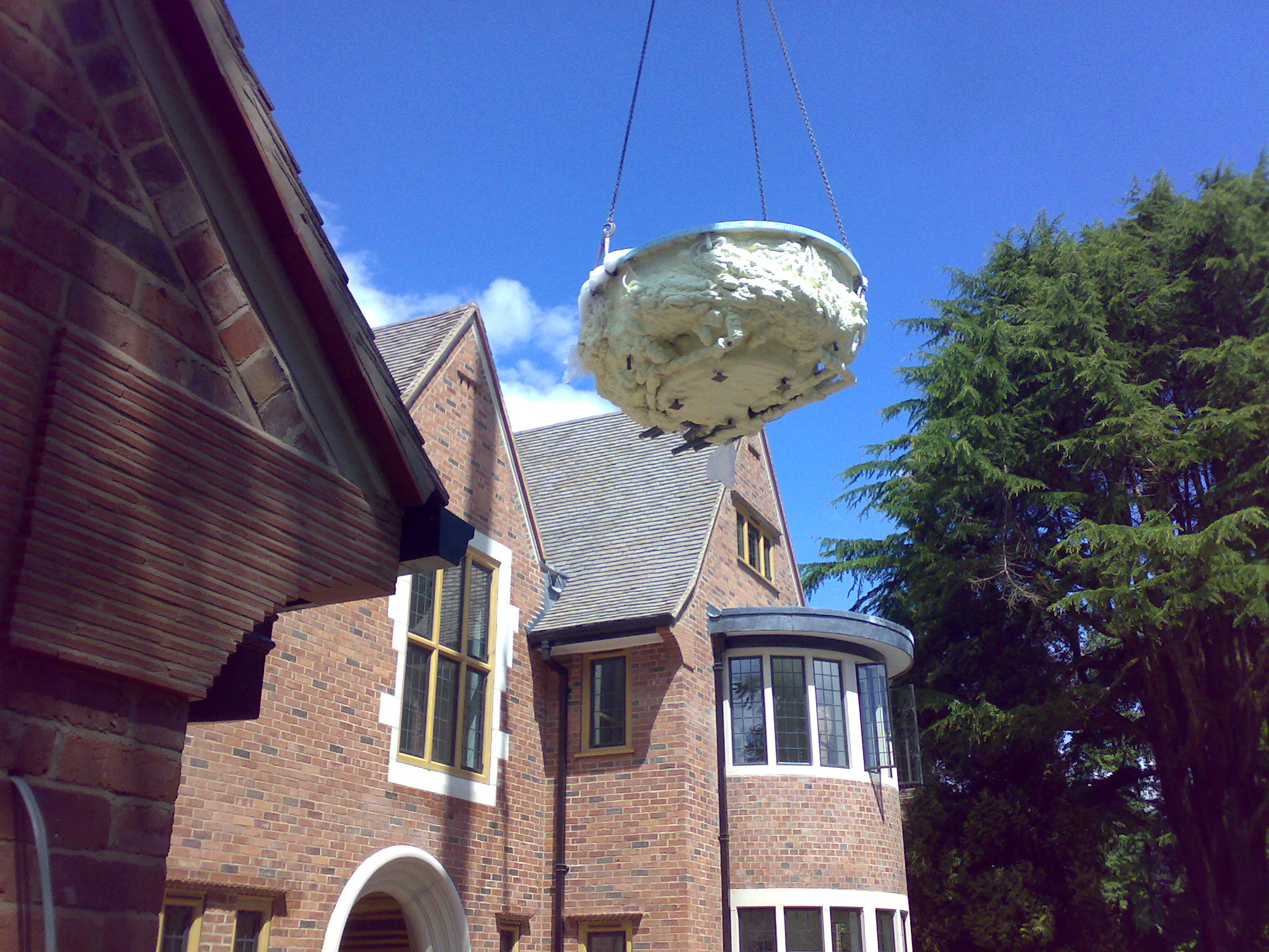 Spa being craned over house to reach pool hall