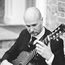 Alex Lloyd Williams playing guitar, black suit