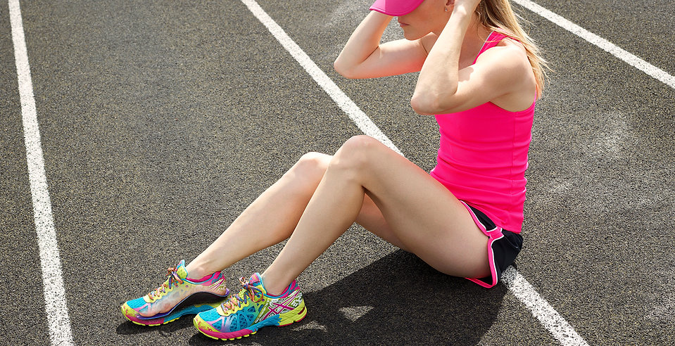 A woman on the track, wearing running shoes with Sore Dawgs Replacement Insoles.