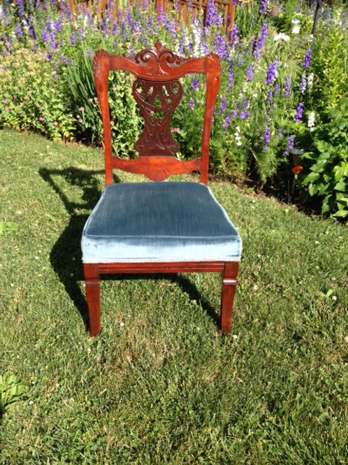Ornate wood chair with blue velvet seat