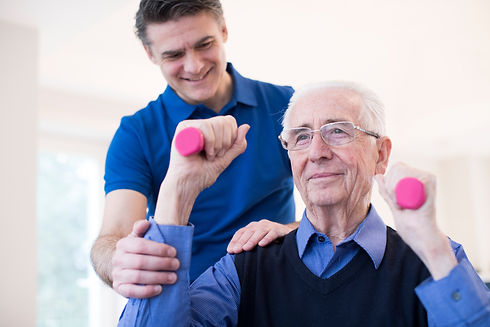Physiotherapist Helping Senior Man To Li