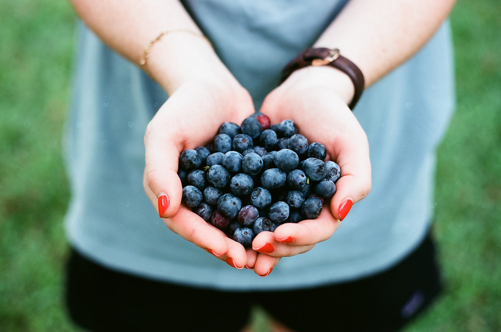 Woman with her hands full of blueberries