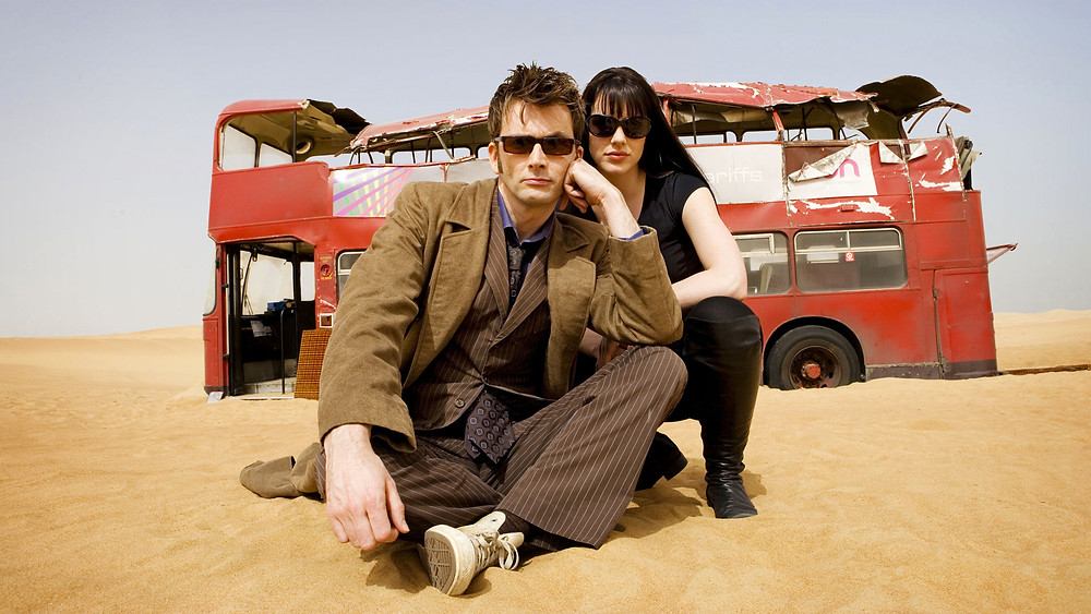 The Tenth Doctor with a bus in the desert