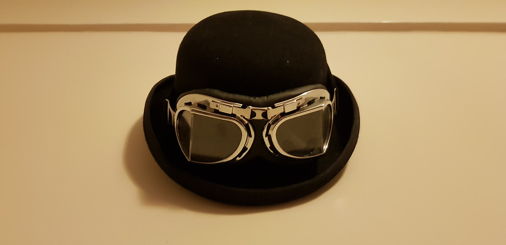 A bowler hat with flying goggles strapped around it.
