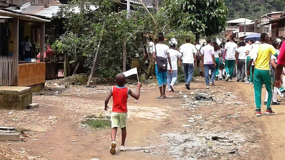 Niño marcha con una bandera blanca por las calles de Ciudad Mutis. Foto: Cortesía