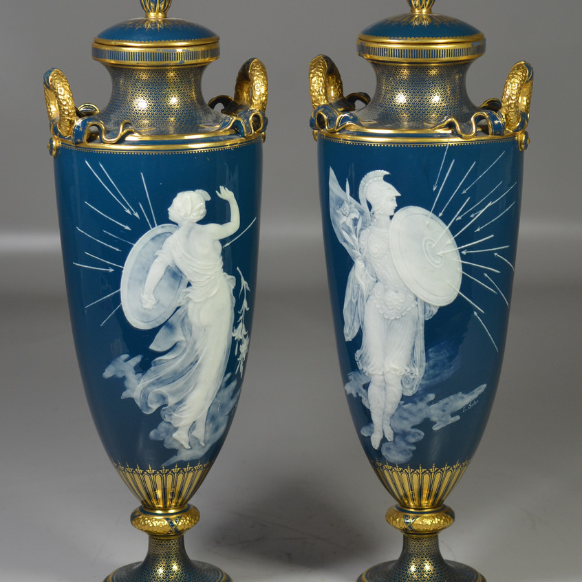 """Pair of Mintons Louis Solon Decorated Pate-sur-Pate Vases and Covers, England, late 19th century, each with gilded wreath-form handles adorned with ribbons, gold fish scale borders to neck and socle, dark teal blue ground with white slip allegorical figures holding shields against Cupids arrows being fired by winged cherubs, with gold globe & Mintons /England mark, c 1891-1912, 15-1/2"""" h"""
