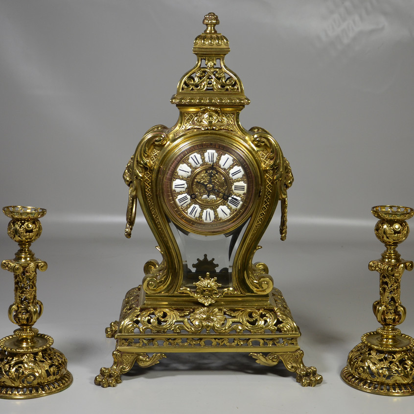 """3 pc French Louis XIV style Tiffany & Co, New York bronze clock set, the lyre shaped case with inset beveled glass panels, the case with ornate C-scroll and shell motifs, lion head and ring handles, all on paw feet, 20-1/2"""" h, with a pr bronze candlesticks by Alphonse Giroux, Paris, pierced pelican decoration aorund base, pierced foliate stems with ladies heads 9-7/8 """"tall, the bronze pendulum with ladies head, late 19th c, back plate of movement marked Tiffany & Co / New York"""